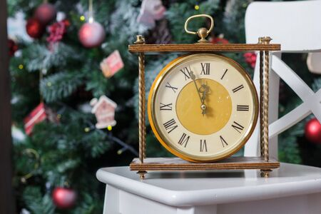 New year is soon. Retro clock on the white chair with the christmas tree on background