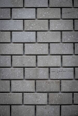 Gray ceramic bricks on the wall as background.