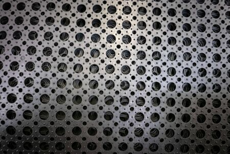 Perforated metal pattern background. Black and gray metal background