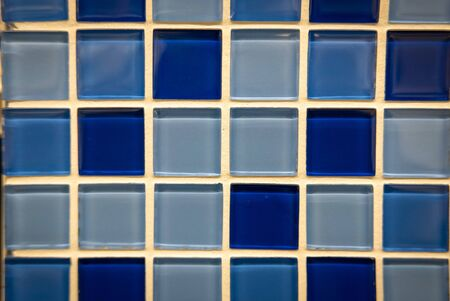 Blue ceramic mosaic on the wall as background.