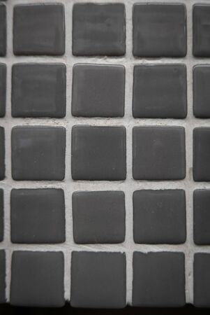 Gray ceramic mosaic on the wall as background. 版權商用圖片