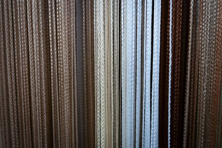 Textile strings and ropes hangs in a fabric shop. Abstract background