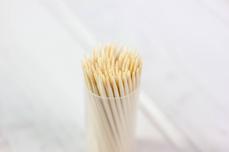 Bamboo toothstick in a case over the white table. Great photo for your needs.