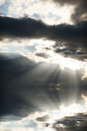 bright sun rays coming through the clouds and falling on sea water Imagens