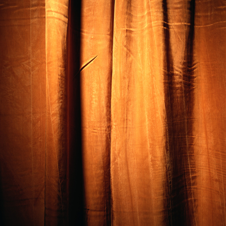 orange and yellow shiny curtain cloth material texture background with glitters