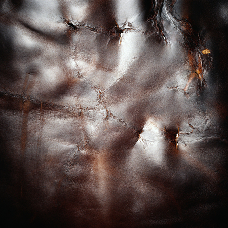 damaged shiny dark brown animal leather texture material background