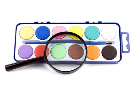 magnifying lens and paints on the white background photo