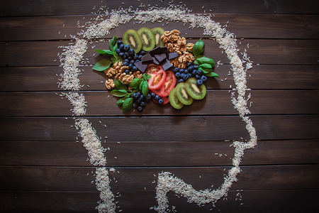 Some nuts, blueberries, dark chocolate, kiwi and tomatoes that are healthy foods for you body and brain.
