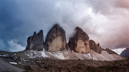 three peaks of three peaks of lavaredo with snow and clouds Banco de Imagens