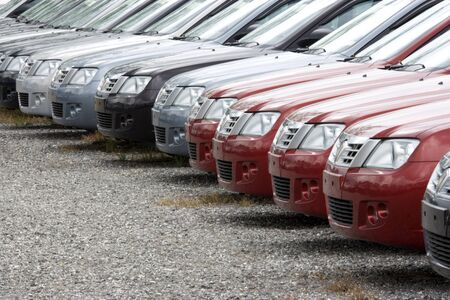 motorcars: A row of brand new motorcars at a stockyard awaiting delivery.