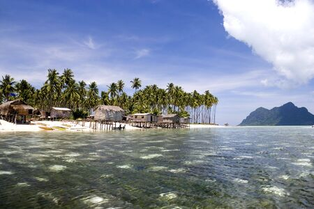 redang: Image of remote Malaysian tropical islands with deep blue skies, crystal clear waters, atap huts and coconut trees.