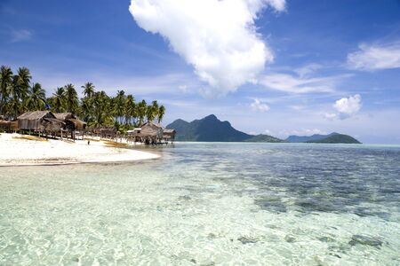 redang: Image of a remote Malaysian tropical island with deep blue skies, crystal clear waters, atap huts and coconut trees. Stock Photo