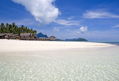 Image of a remote Malaysian tropical island with deep blue skies, crystal clear waters, atap huts and coconut trees. photo