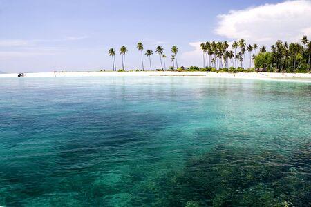 Image d'une île tropicale de Malaisie à distance avec un ciel d'azur, ses eaux limpides et des cocotiers.