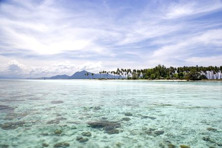 Image of remote Malaysian tropical islands with deep blue skies, crystal clear waters, atap huts and coconut trees. photo