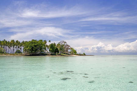 Image of a remote Malaysian tropical island with deep blue skies, crystal clear waters and coconut trees. photo