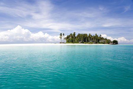 Afbeelding van een externe Maleisische tropisch eiland met diep blauwe luchten, kristal helder water, atap hutten en kokos palmen.  Stockfoto