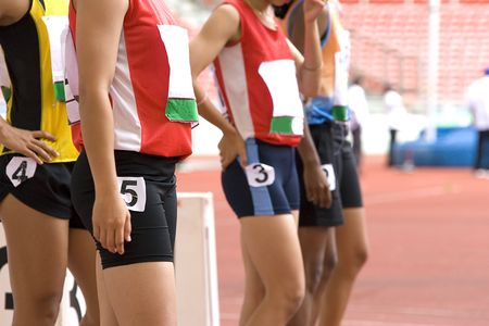 Image of female 100 meter athletes awaiting the start of their race. Stock Photo