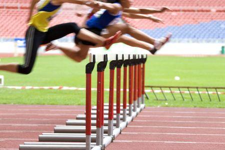 Bild von Hürden in Aktion in einem Stadion mit absichtlich verwischt zu porträtieren Geschwindigkeit.