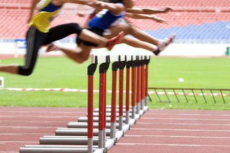 hurdles: Image of hurdles in action at a stadium with intentional blurring to portray speed.