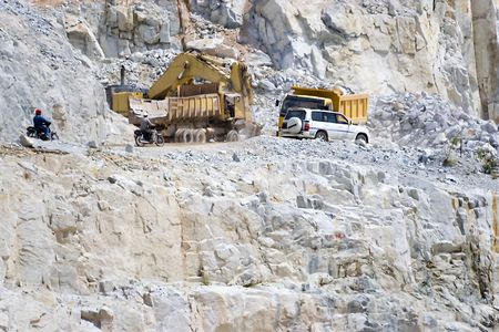 heavy machinery: Image of a heavy machinery and vehicles at a granite rock quarry in Malaysia.
