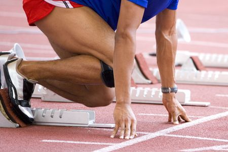 Image of a 100 meters athlete at the starting block.