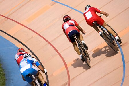 unison: Image of participants in a cycling points race held at a velodrome. Stock Photo