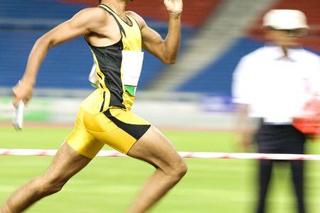 pista de atletismo: Imagen de un atleta de 4x400 metros en la acci�n intencional con algunos borrando a representar la velocidad. Foto de archivo