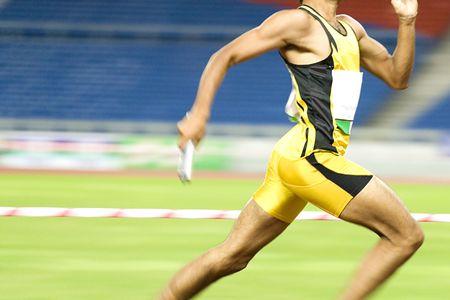 atletismo: Imagen de un atleta de 4x400 metros en la acci�n con algunos desenfoque intencional para describir la velocidad.