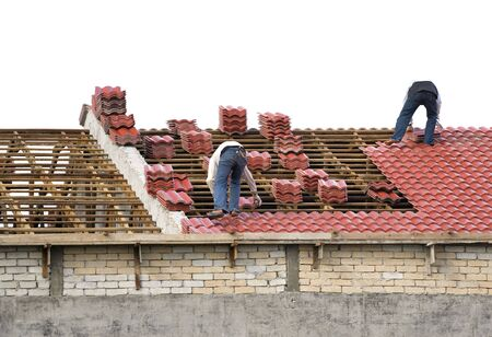 Image of workers laying roof tiles on an house under construction. photo