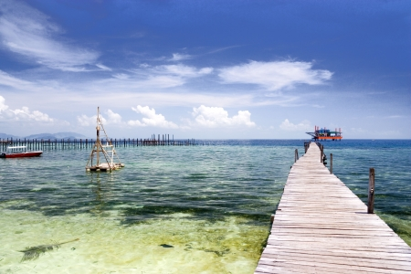 Image of a jetty against a backdrop of a beautiful sea, sky and an oil rig in Malaysia. Stock Photo