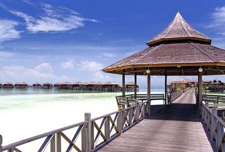 zancos: Imagen de un pasillo y chozas sobre pilotes en una remota isla tropical de Malasia con el cielo azul profundo y aguas cristalinas. Foto de archivo