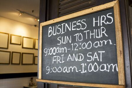 opening hours: Business opening hours signboard on display. Stock Photo