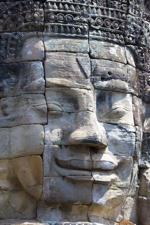 cambodia sculpture: Image of Buddhas face at UNESCOs World Heritage Site of Bayon, which is part of the larger temple complex of Angkor Thom, located at Siem Reap, Cambodia. This is one of the temples in Siem Reap where the Hollywood movie Lara Croft Tomb Raider was filmed