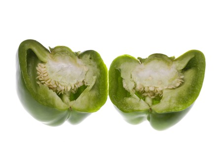 hottest: Isolated macro image of a sliced green capsicum.