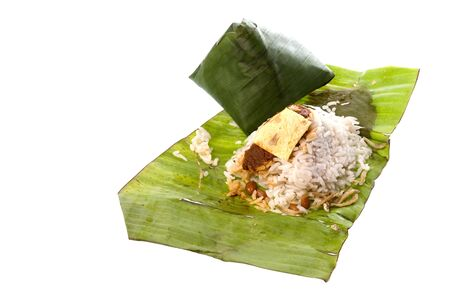 Isolated image of rice cooked in coconut milk and packed in banana leaf, commonly known as Nasi Lemak. This Malaysian delicacy is served with spicy paste, anchovies, groundnuts, cucumber slices, and is usually taken in the morning for breakfast. photo