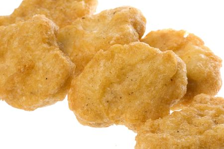 nugget: Isolated macro image of fried chicken nuggets.