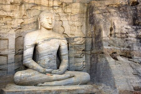 Image of a seated Buddha sculpture at Gal Vihara, Polonnaruwa, Sri Lanka. The colossal Buddha image, a masterpiece of Sri Lankan Buddhist art, was carved on the face of a granite boulder, commissioned by Parakramabahu I (1153-1186 AD). This is a UNESCO Wo