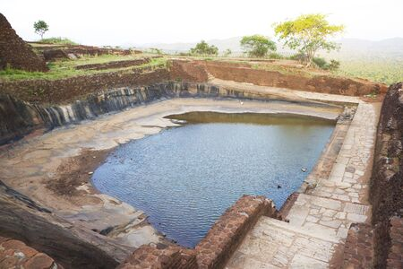 Image of an ancient cistern that still retains water at UNESCOs World heritage site of Sigiriya (Lions Rock), Sri Lanka. This is an ancient rock fortress and palace ruin built during the reign of King Kassapa I (477-495 AD). photo