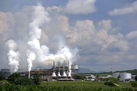 Image of a palm oil factory with an oil palm estate in the foreground at Johore, Malaysia.  photo