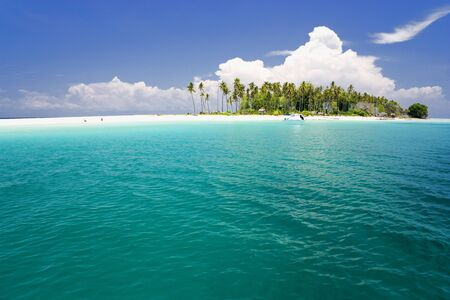 Image of a remote Malaysian tropical island with deep blue skies and crystal clear waters.