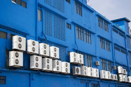 con: Image of aircondition compressors on a blue building.