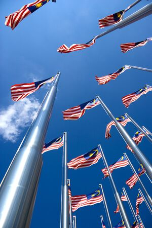 flagpoles: Image of Malaysian flags, also known as Jalur Gemilang, flying high. Stock Photo