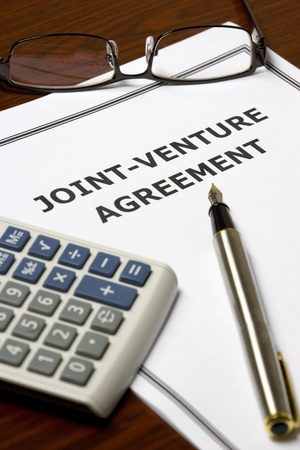 contractual: Image of a joint-venture agreement on an office table.