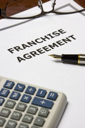 contractual: Image of a franchise agreement on an office table.