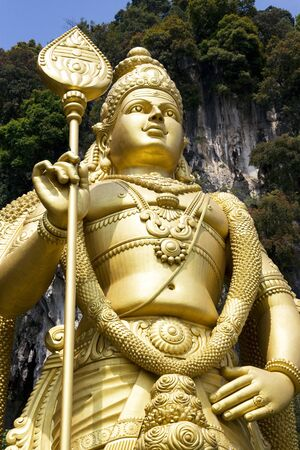 godliness: Image of the worlds tallest (42.7 meters) statue of Lord Muruga, a Hindu deity. Located at Batu Caves Temple, Selangor, Malaysia. Stock Photo