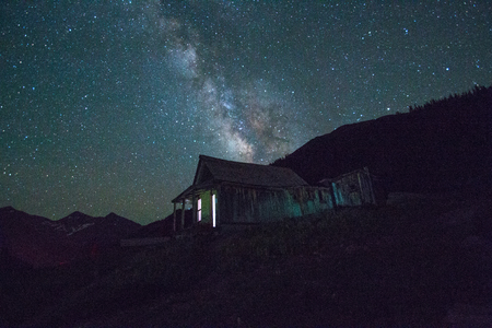ghost town: an old ghost town building lit up under the Milky Way