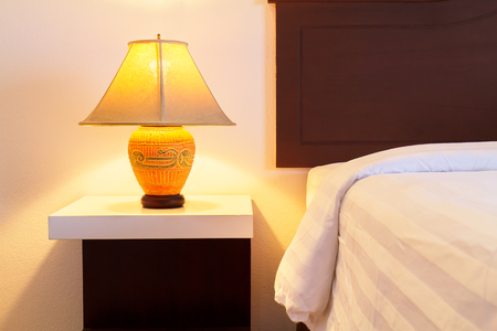 switched: Lamp on a night table with  light switched on beside the bed in the cozy bedroom