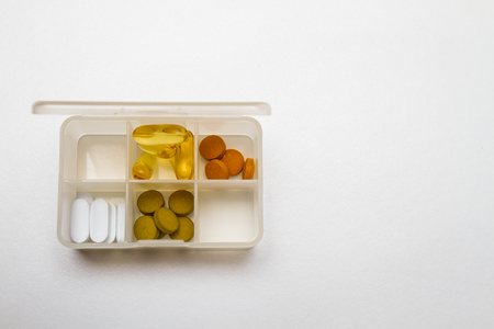 pill box: Pill box with some pills in the box on white background Stock Photo