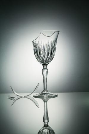 Broken crystal  glass with reflection on white illuminated background Stock Photo